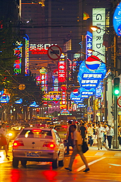 Shoppers in neon lit streets, Shanghai, China, Asia