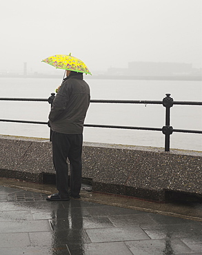 A man waits in the rain under a childs umbrella, United Kingdom, Europe