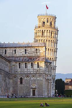 People relaxing on the lawns of the Campo dei Miracoli with the Cathedral and Leaning Tower behind, UNESCO World Heritage Site, Pisa, Tuscany, Italy, Europe