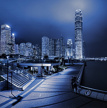 Central and Western district promenade leads through to skyscrapers on Hong Kong island above Victoria Harbour at night, Hong Kong, China, Asia