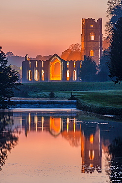 The Cistercian monastery of Fountains Abbey lit at dusk and reflected in the River Skell, UNESCO World Heritage Site, North Yorkshire, Yorkshire, England, United Kingdom, Europe