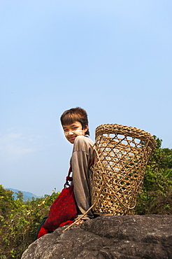 A boy with a doko (back basket) wearing powdered sandalwood on his face for decoration, Kachin State, Myanmar (Burma), Asia