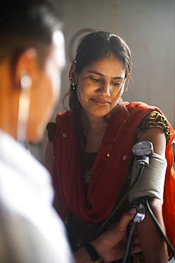 A doctor takes a woman's blood pressure in a hospital in Nepal, Asia