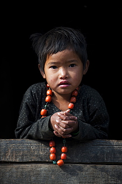A little girl plays with her necklace in the Manaslu region of Nepal, Asia