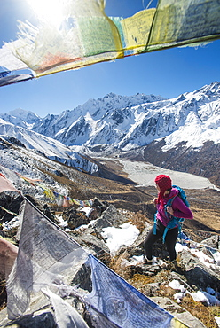 A woman trekking in the Langtang valley in Nepal stands on the top of Kyanjin Ri and looks out towards Ganchempo in the distance, Langtang Region, Nepal, Asia