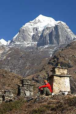 A trekker stops beside a chorten to admire the views on the way to Everest Base Camp with views of Taboche in the distance, Khumbu Region, Himalayas, Nepal, Asia