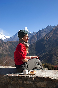 A trekker stops on the trail for some fuel, with Ama Dablam is the peak visible in the distance, Khumbu Region, Nepal, Asia