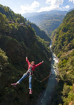 A girl jumps a canyon swing, Nepal, Asia