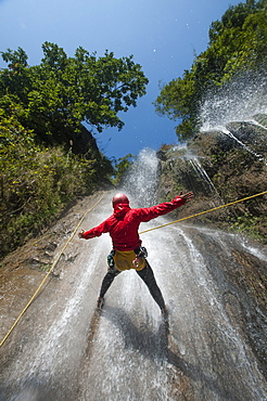 A man pauses to hold his arms in the falling water while canyoning, Nepal, Asia
