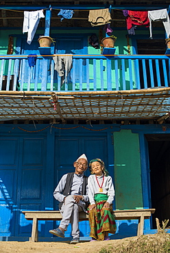 A old Nepali couple wearing traditional dress sit outside their house in Diktel, Khotang District, Nepal, Asia
