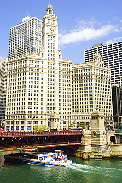 Sightseeing boat passing under DuSable Bridge on the Chicago River with Wrigley Building behind, Chicago, Illinois, United States of America, North America