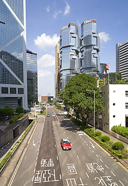 Red taxi cab in Central, Hong Kong Island, with the Bank of China Tower and Lippo Centre beyond, Hong Kong, China, Asia