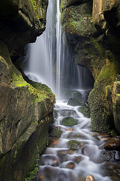 Hidden waterfall in the cliffs behind Singing Sands Beach, Cleadale, The Isle of Eigg, Small Isles, Inner Hebrides, Scotland, United Kingdom, Europe