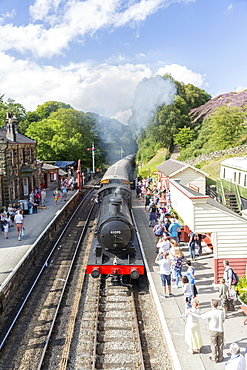 Goathland station and a steam locomotive pulling in from Grosmont, on the North Yorkshire Moors Steam Railway, Goathland, Yorkshire, England, United Kingdom, Europe