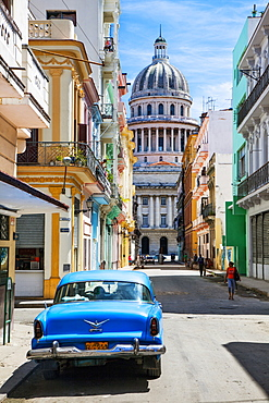 A classic car parked on the street next to colonial buildings with the former Parliament Building in the background, Havana, Cuba, West Indies, Caribbean, Central America