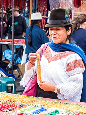 Indigenous woman buying gold necklace, market, Plaza de los Ponchos, Otavalo, Ecuador, South America