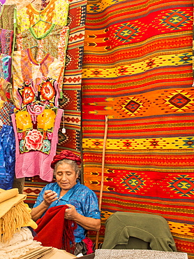 Woman sewing in market with background of handmade rugs, Oaxaca, Mexico, North America