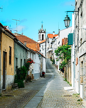 Narrow cobblestone street looking towards Santiago Church in Belmonte, Castelo Branco, Portugal, Europe