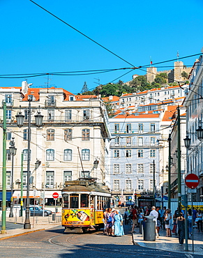 Traditional yellow tram at Praca da Figueira with Castelo Sao Jorge at background, Lisbon, Portugal, Europe