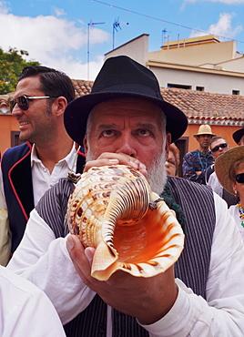 Man blowing conch shell, Romeria de San Benito de Abad, traditional street party, San Cristobal de La Laguna, Tenerife Island, Canary Islands, Spain, Europe