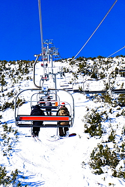 Borovets Ski Resort, a skier and snowboarder sit on Markudjik ski lift, Bulgaria, Europe