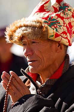 Man praying at the Jokhang Temple of Barkhor Square, Lhasa, Tibet, China, Asia