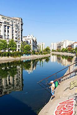 A fisherman on the Dimbovita River in Bucharest, Romania, Europe