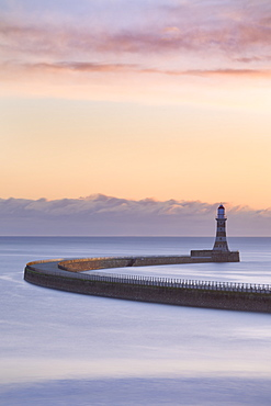 The colours of a winter sunrise over the curving pier and lighthouse at Roker, Sunderland, on the North East Coast, England, United Kingdom, Europe