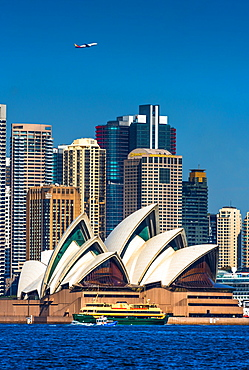 An airplane flies over the Sydney city skyline and Opera House as a ferry and water taxi pass by, Sydney, New South Wales, Australia, Pacific