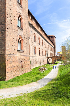 Two people walk in the park of Castello Visconteo (Visconti Castle), Pavia, Pavia province, Lombardy, Italy, Europe