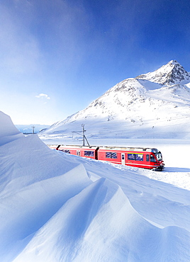 Bernina Express transit along Lago Bianco during winter blizzard, Bernina Pass, Engadine, Graubunden canton, Switzerland, Europe