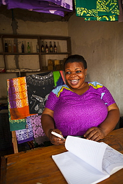 A woman smiling behind the counter of her shop, Tanzania, East Africa, Africa