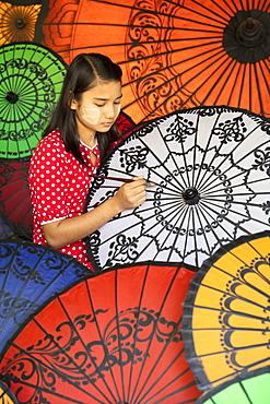 Young lady decorates colourful parasols in Bagan (Pagan), Myanmar (Burma), Asia