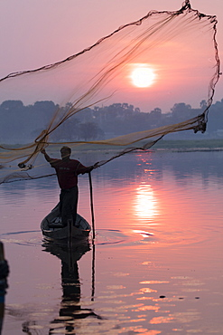 Fisherman casts his net at sunrise on Lake Taungthaman near U Bein Bridge, Myanmar (Burma), Asia
