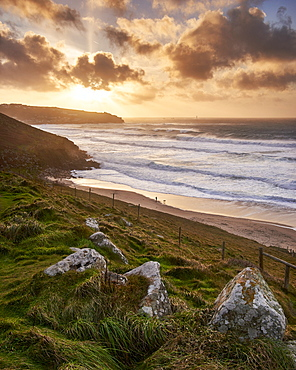 A winter dog walker watches the waves in a gale on the beach Gwenver near Sennen in Cornwall, England, United Kingdom, Europe