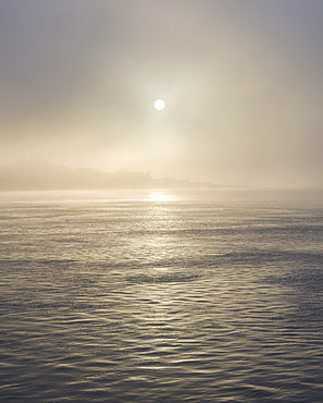 The sun shines through heavy fog on the sea front at Exmouth, Devon, England, United Kingdom, Europe