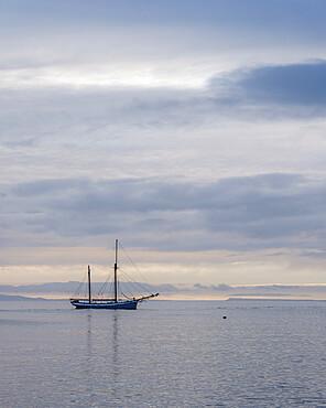 Yacht anchored off The Cobb in Lyme Regis, Dorset, UK