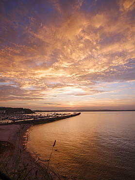Colourful sunset view of Breakwater Beach and the harbour wall of Brixham, Devon, England, United Kingdom, Europe