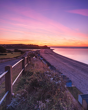 Colourful dawn with sweep of the shoreline, beach huts, pebbles and the cliff of Otter Head at Budleigh Salterton, Devon, England, United Kingdom, Europe