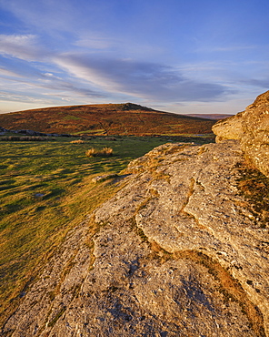First sunlight on granite at the summit of Saddle Tor looking at Rippon Tor, Dartmoor National Park, Bovey Tracey, Devon, England, United Kingdom, Europe