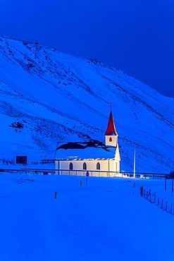 Floodlit church at dawn against snow covered mountains, winter, near Vik, South Iceland, Iceland, Polar Regions