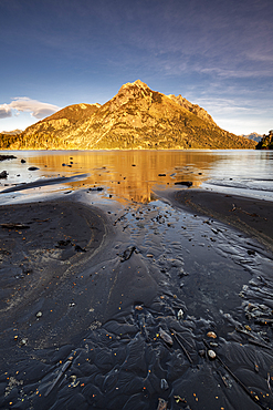 Black lava beach with reflected mountain, Barilochie, Patagonia, Argentina, South America