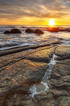 Spectacular sunrise at The Moeraki Boulders, Moeraki Beach, Otago, South Island, New Zealand, Pacific
