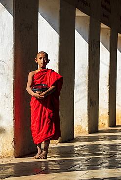 Novice Buddhist monk holding a bowl in Shwezigon Pagoda in Nyaung U, Bagan (Pagan), Myanmar (Burma), Asia