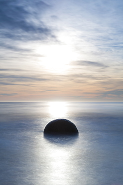 A single Moeraki Boulder at sunrise with long exposure, Moeraki Beach, Otago, South Island, New Zealand, Pacific