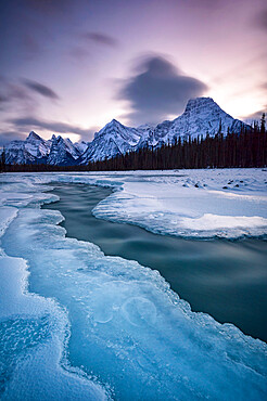 The Athabasca River in winter with mountain backdrop, Alberta, Canada, North America