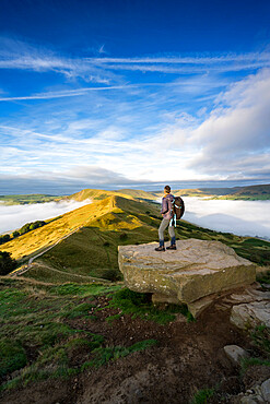 A walker stood looking across The Great Ridge during a cloud inversion with view of Mam Tor, Hope Valley, Derbyshire