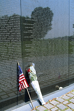 Flag and flowers against the list of names on the Vietnam Veterans Memorial in Washington D.C., United States of America, North America