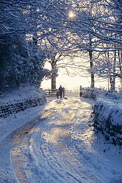Man and child walking down a snow covered road in winter near Arthington, West Yorkshire, England, United Kingdom, Europe
