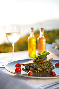 Spanikopita with white wine at sunset at a restaurant in Pefkos, Rhodes, Dodecanese, Greek Islands, Greece, Europe